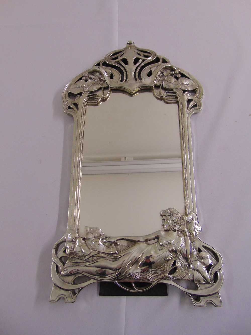 Lot 41 - A silvered Art Nouveau style table mirror shaped rectangular with stylised vegetation and a