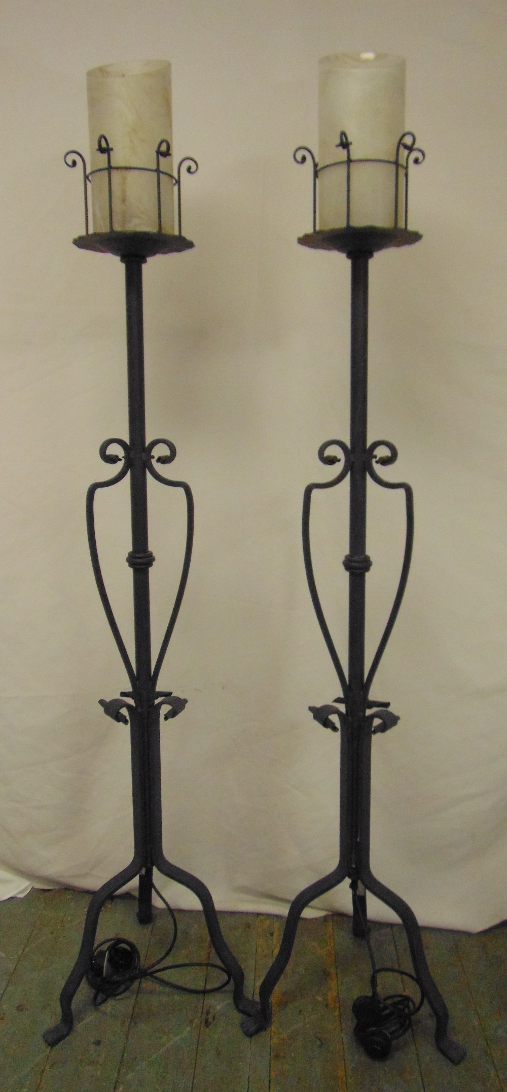 Lot 49 - A pair of painted wrought iron candle holders converted to electricity on three scroll supports