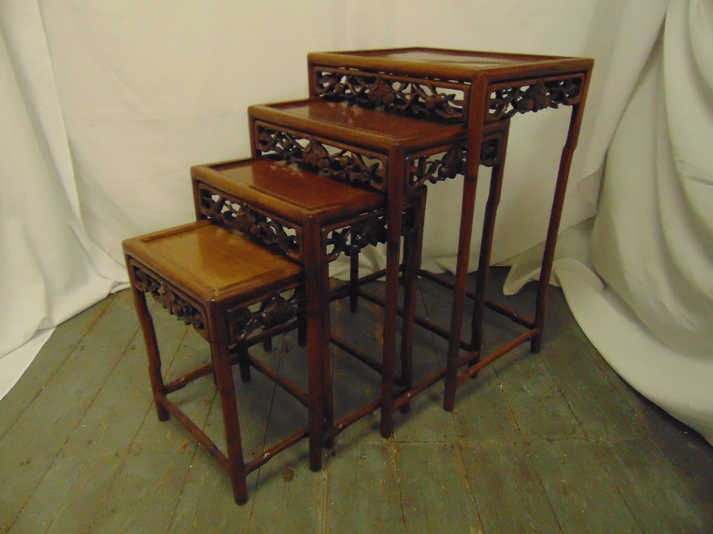 Lot 11 - A 20th century quartetto of Chinese hardwood nesting tables of rectangular form with foliate