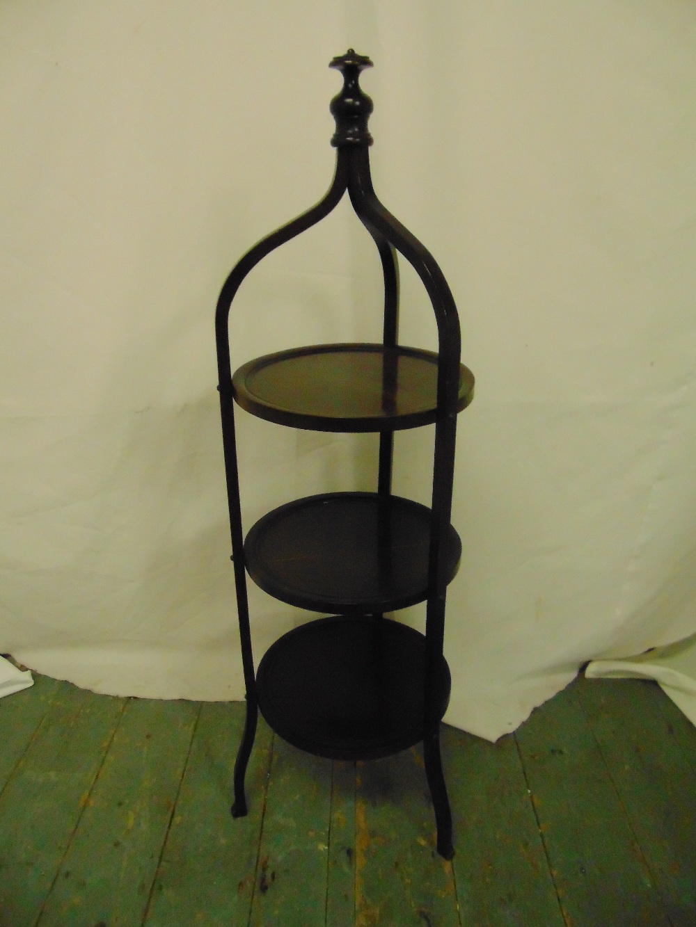 Lot 23 - A three tier mahogany tea stand surmounted by baluster finial on three scrolling legs