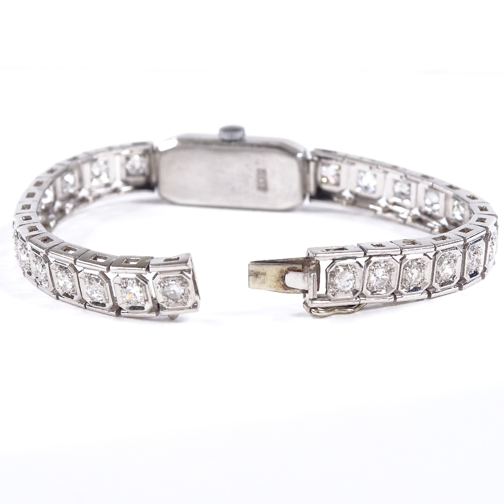 Lot 474 - A lady's platinum and diamond encrusted cocktail wristwatch, total diamond content approx 2ct,