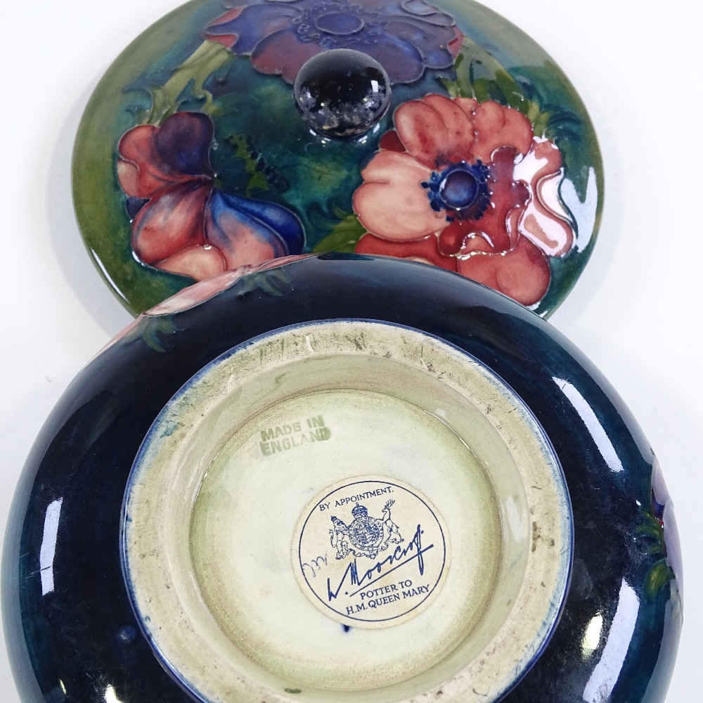Lot 22 - Moorcroft Pottery, circular anemone pattern pot and cover, original paper label, diameter 14cm