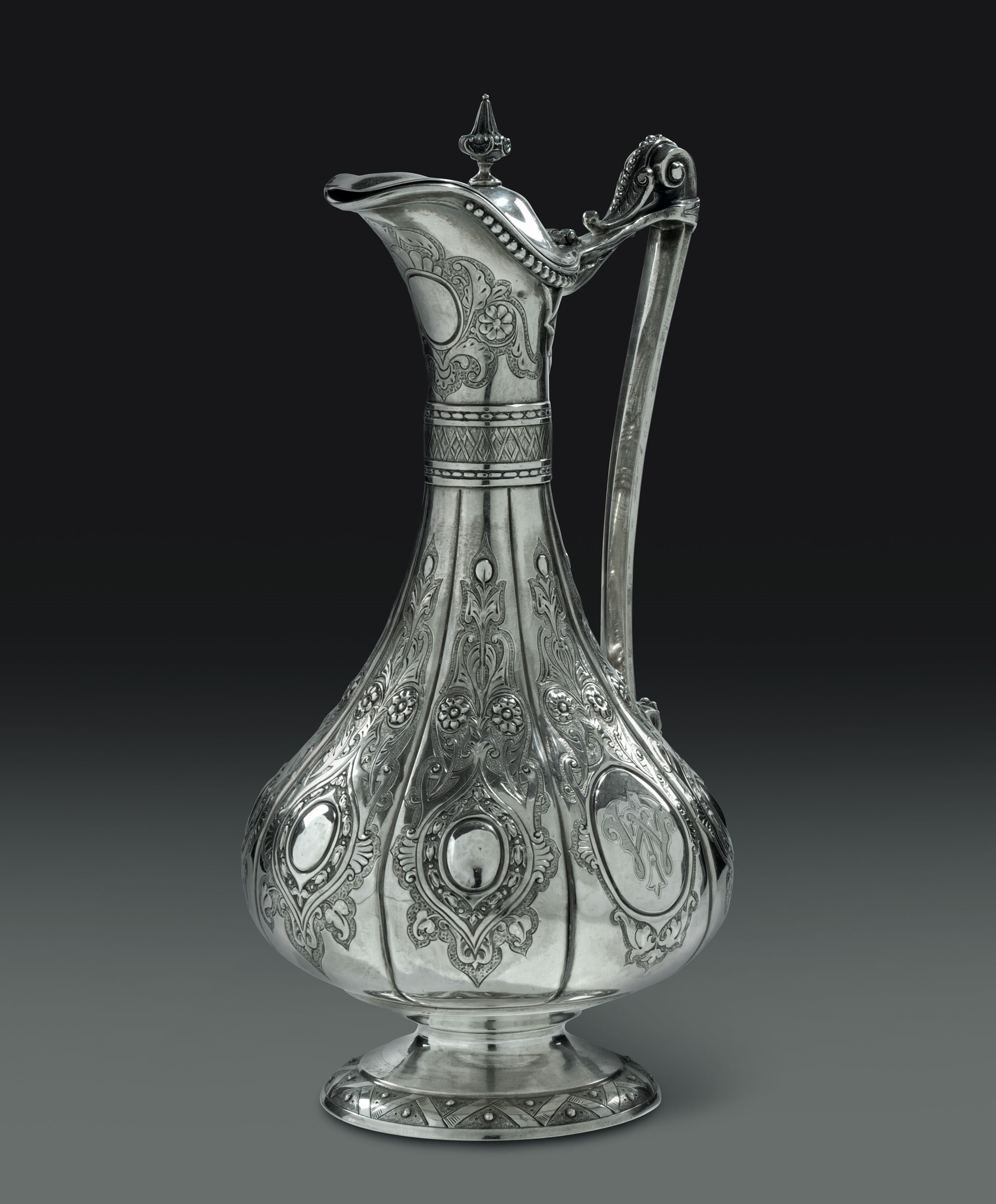 Lot 49 - A pitcher in embossed and chiselled silver, London 1881 ca. - - altezza cm 35, gr. [...]