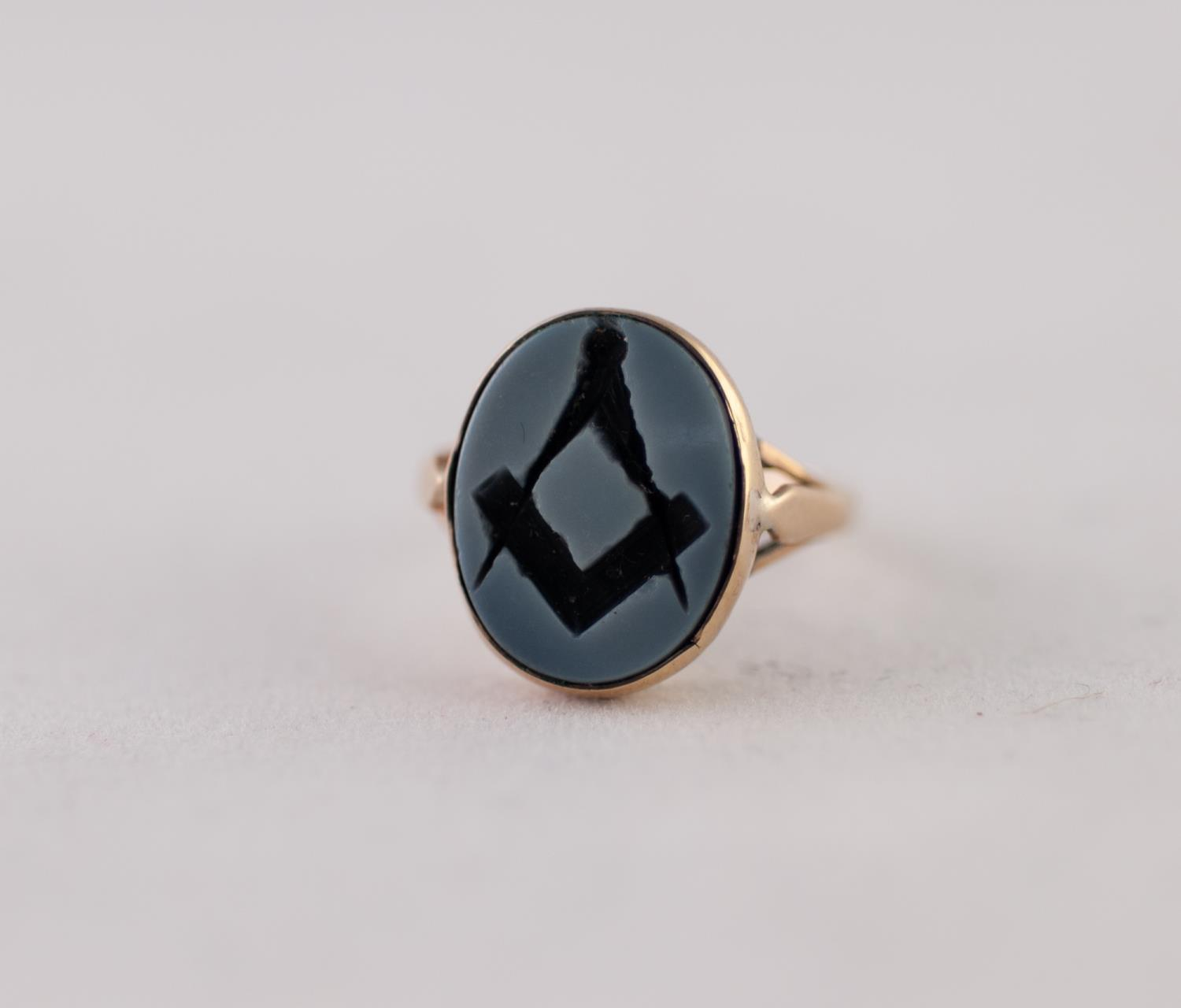 Lot 223 - SARDONYX MASONIC INTAGLIO RING. An oval plaque with engraved Masonic motif, to forked shoulders,