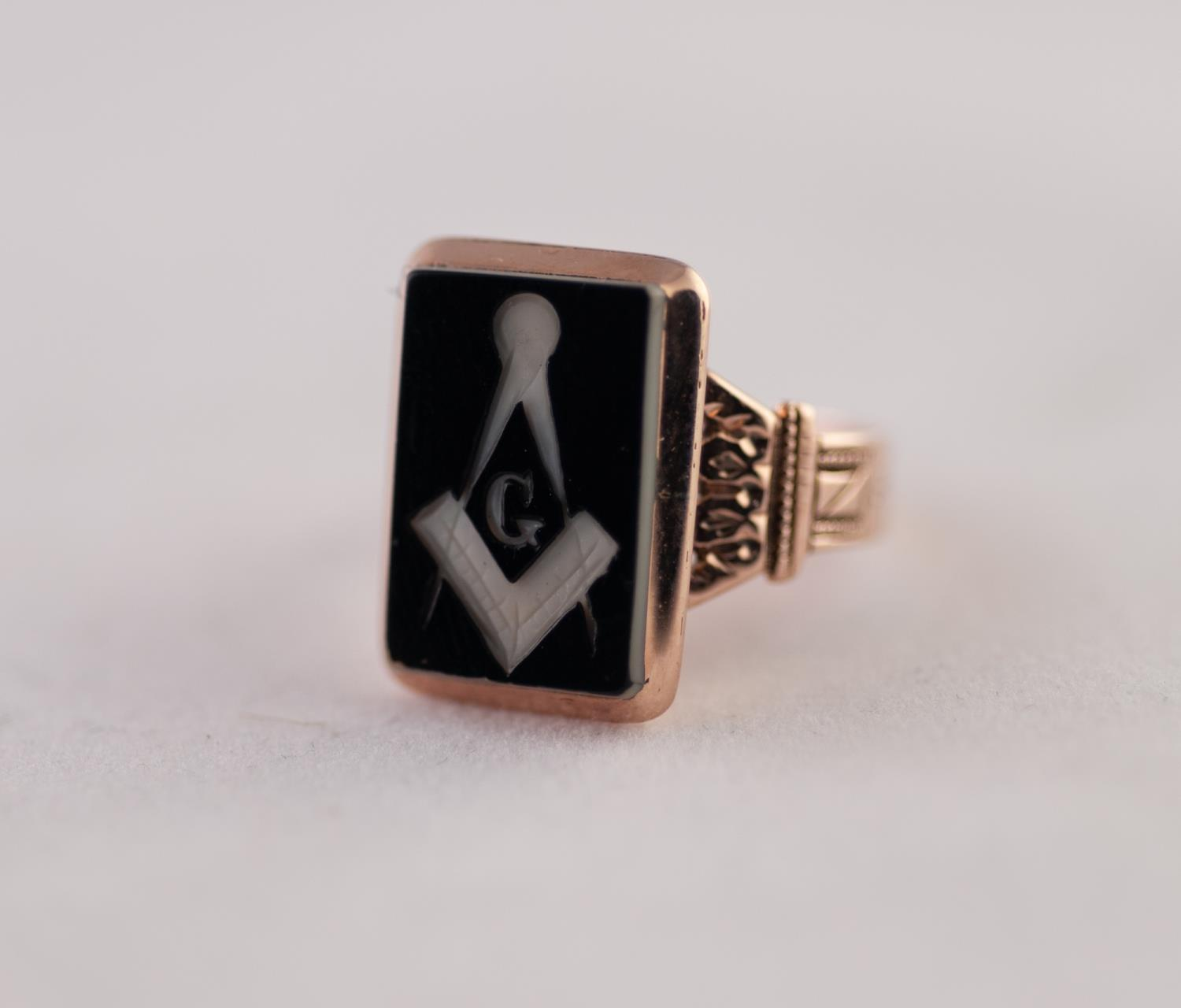 Lot 225 - A MASONIC INTALGIO SIGNET RING, a rectangular plaque with an engraved Masonic motif, to fancy