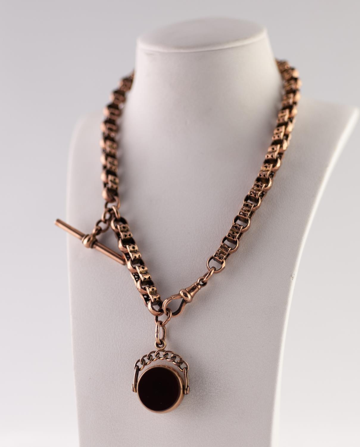 Lot 203 - GOLD FANCY LINK ALBERT CHAIN, of pierced lobed links, with T-bar, clip and a 9ct gold hardstone