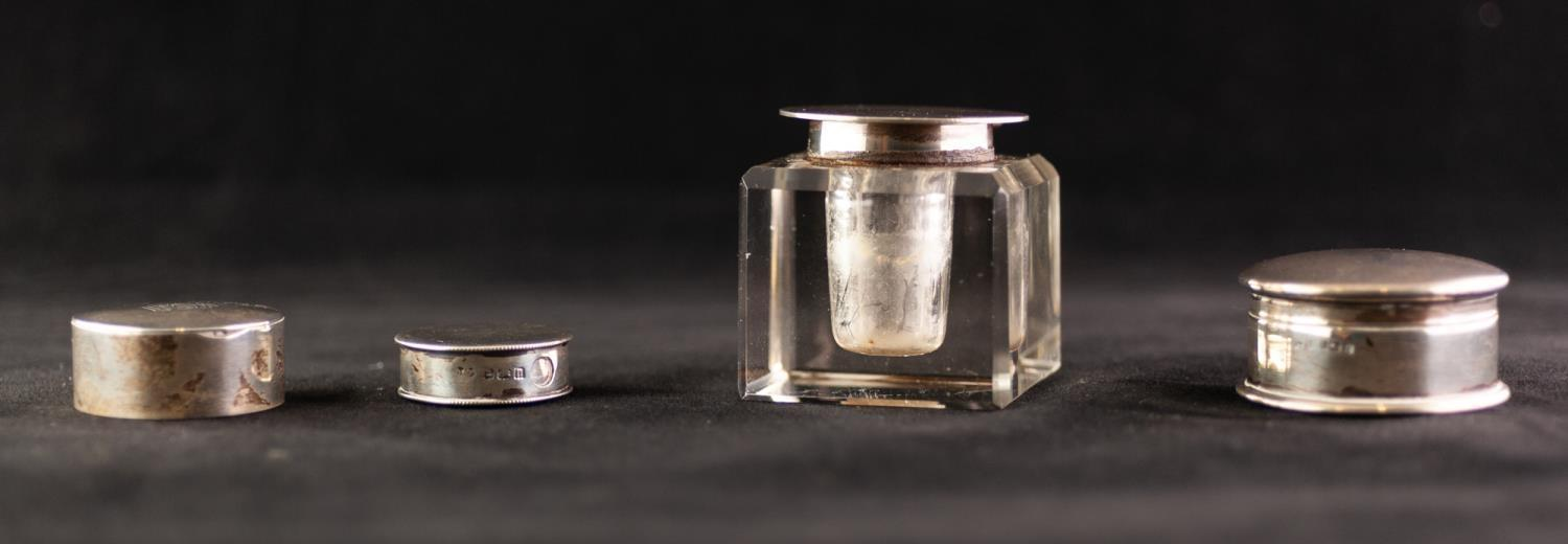 Lot 517 - A SQUARE CUT GLASS INKWELL with silver mount, Birmingham 1927, also THREE SMALL SILVER LIDDED