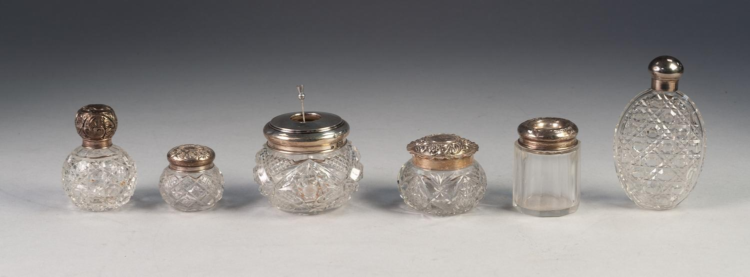Lot 648 - GEORGE V SMALL CUT GLASS ORBICULAR SALTS BOTTLE, with push on embossed silver top, London 1913.