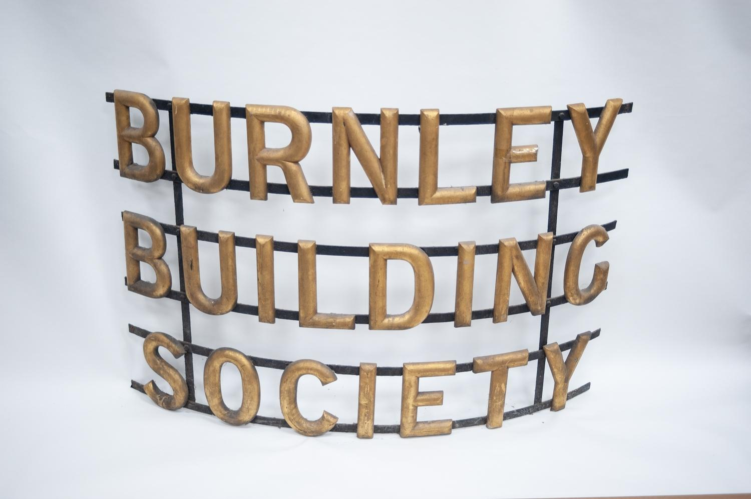 Lot 395 - CURVED WROUGHT IRON ADVERTISING SIGN ?BURNLEY BUILDING SOCIETY?, with gilt lettering on three bands,