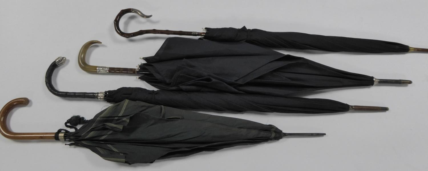 Lot 842 - FOUR EARLY 20th CENTURY UMBRELLAS with silver mounts, one with white metal mounts (4)