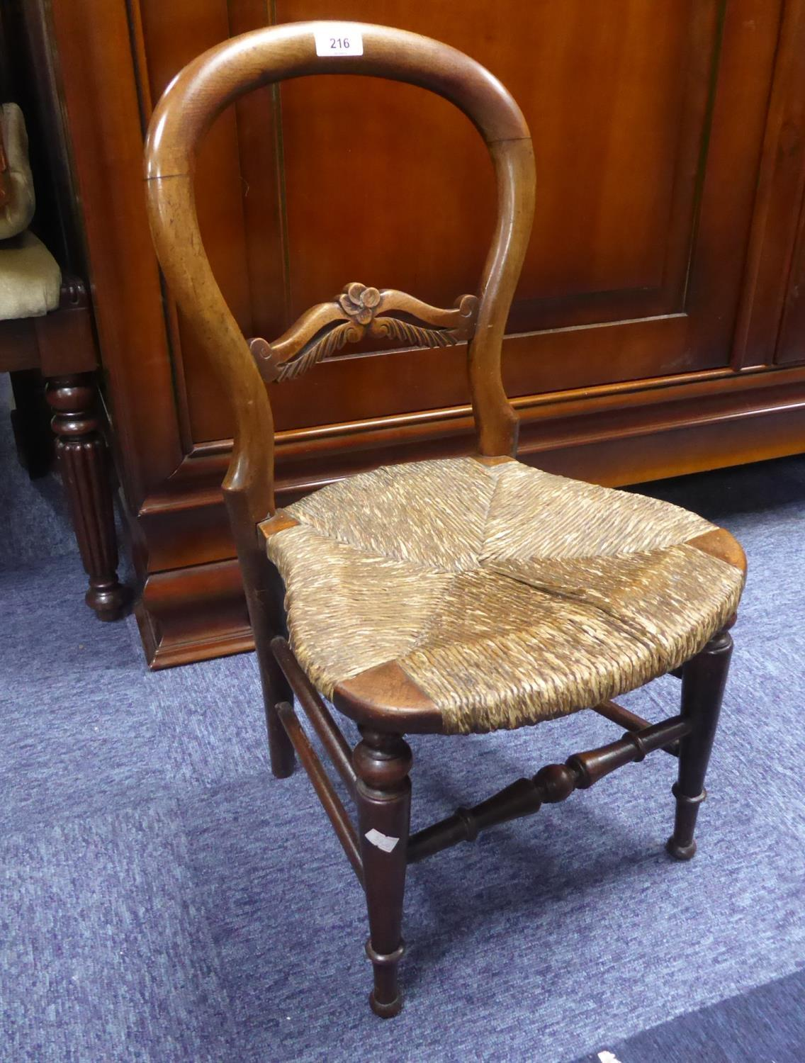 Lot 216 - NINETEENTH CENTURY CARVED WALNUT CHILD'S RUSH SEATED BALLOON BACK CHAIR, of typical form with