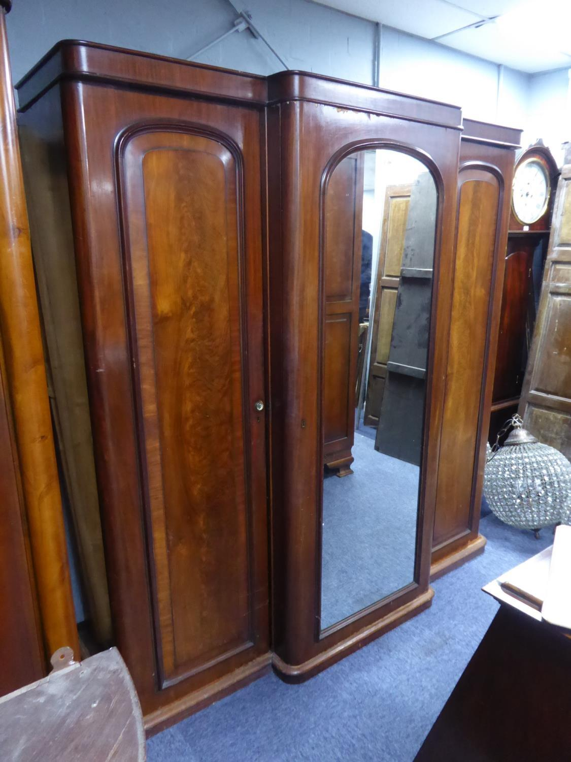 Lot 206 - VICTORIAN FIGURED MAHOGANY THREE DOOR BREAK FRONT WARDROBE OF SMALL PROPORTIONS, the short,