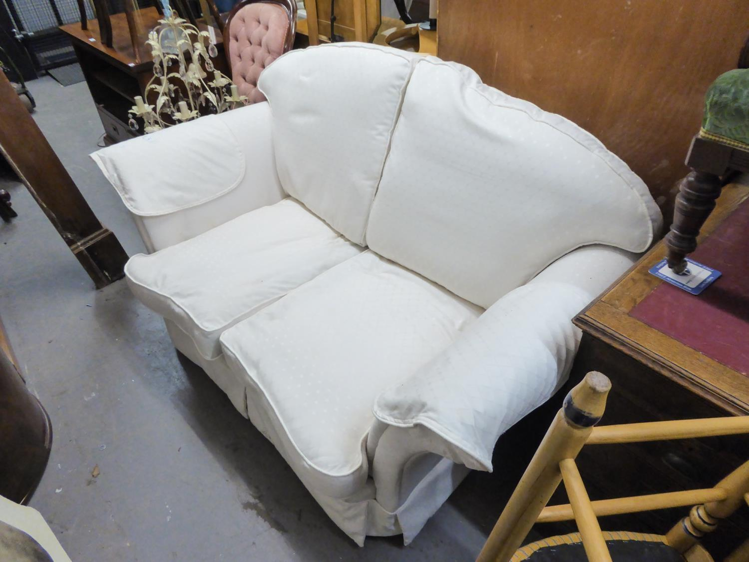 Lot 4 - A TWO SEATER SETTEE COVERED IN WHITE FABRIC, WITH LOOSE CUSHIONS