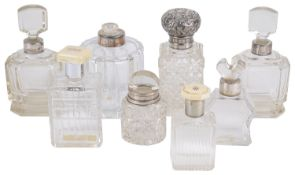 A collection of Edwardian and later glass and silver perfume/cologne bottles
