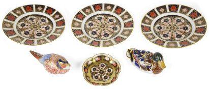 Two Royal Crown Derby Imari bird paperweights, three Imari plates and a trinket dish