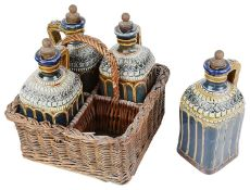 An unusual Doulton stoneware four decanter set in wicker basket