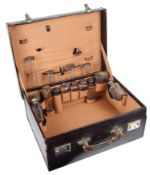 A vintage purple leather vanity case with silver topped glass bottles