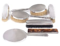 A George VI late Art Deco engine turned silver backed six piece dressing table set