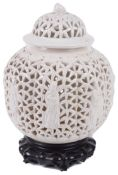 A 19th century Chinese blanc de chine reticulated lobed ginger jar and cove on hardwood stand