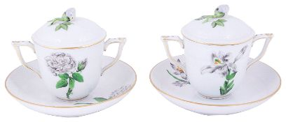 A pair of Herend porcelain twin handled botanical covered chocolate cups and stands