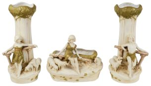 An Austrian Royal Dux blush ivory porcelain figural three piece garniture of vases