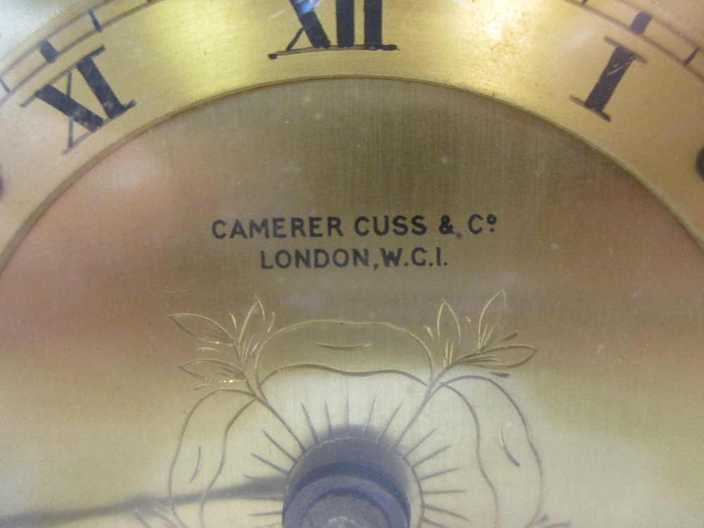 Lot 17 - A coral coloured leather covered mantel clock in the Art deco taste retailed by Cameron Cuss and Co
