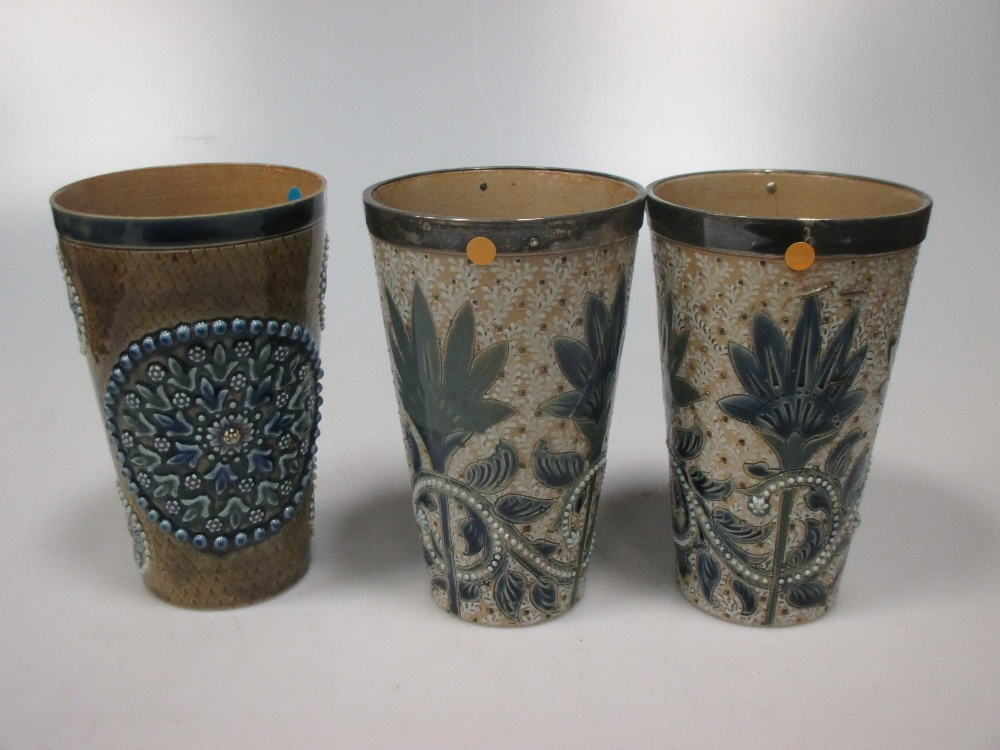 Lot 8 - A pair of Royal Doulton silver mounted pottery beakers, by Florence Barlow (A/F), another similar,