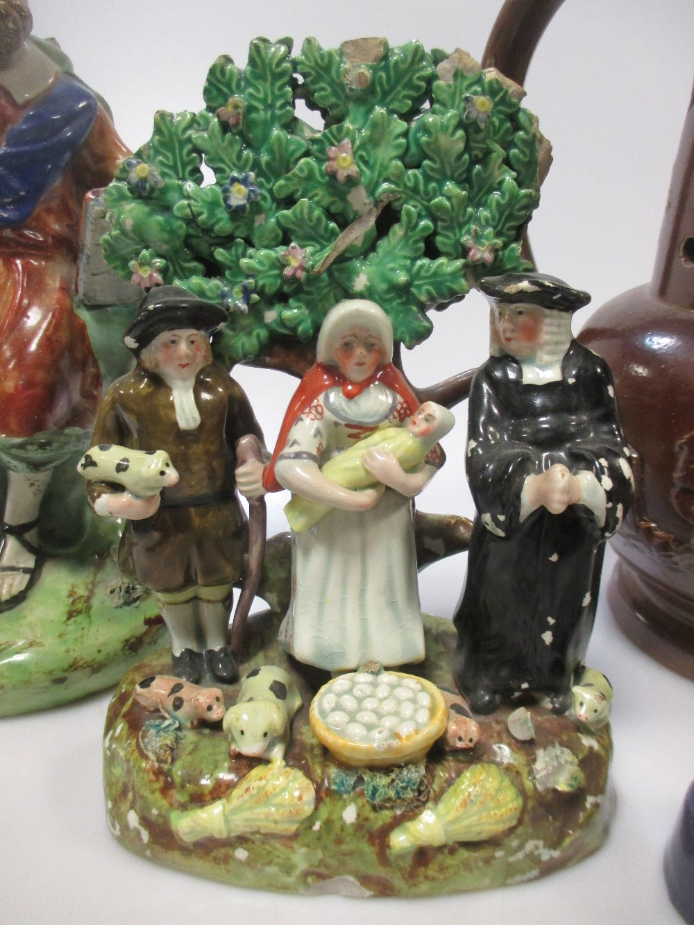 Lot 34 - An 18th century Walton figure of St Paul (A/F), a Staffordshire 'Tythe Pig Group', a 19th century