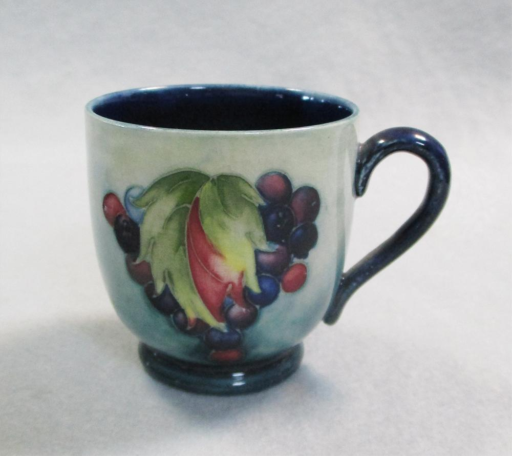 Lot 44 - A Moorcroft Leaves and Berries coffee can and saucer, painted to a pale green ground, impressed