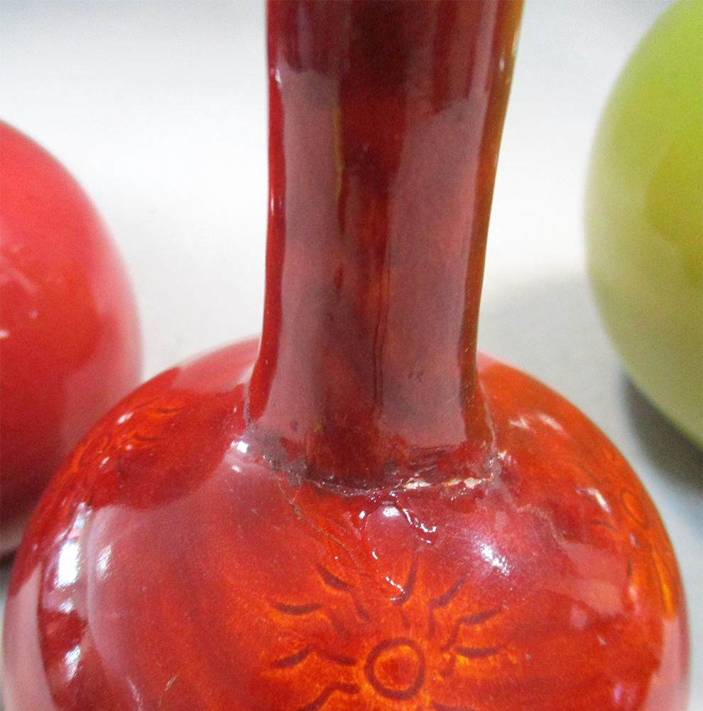 Lot 25 - Four Burmantofts faience vases, comprising a yellow glaze bottle vase, a large red glaze vase, and