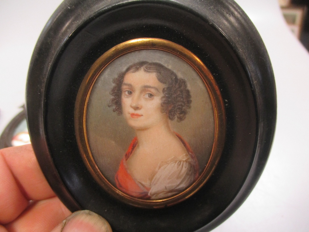 Lot 311 - An early 19th century portrait miniature on ivory of a military officer together with three