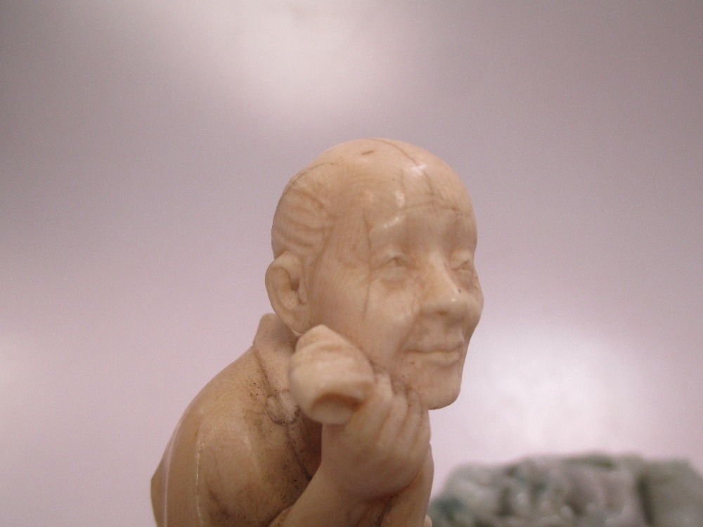 Lot 316 - An early 20th century Japanese ivory figure of an old man with paddle together with a quantity of