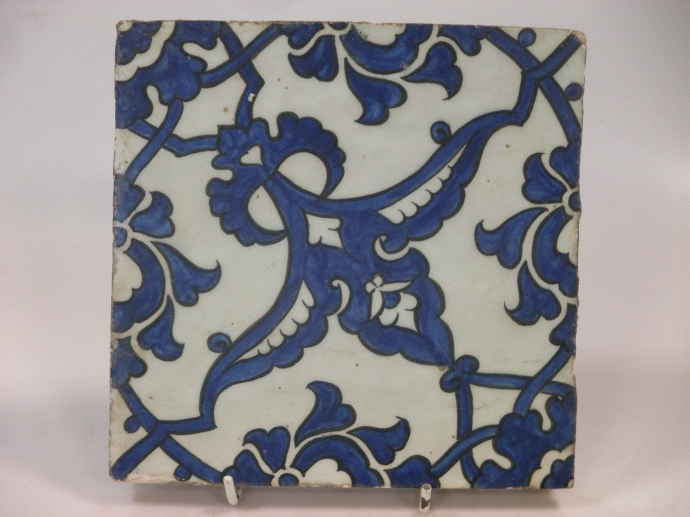 Lot 210 - A mid 16th century Iznik 'Dome of the Rock' tile, painted in blue on the diagonal with wing shaped