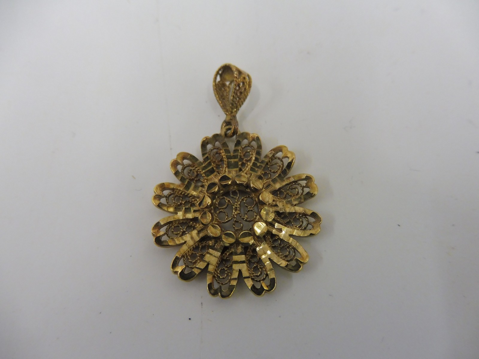 Lot 7 - An unusual 9ct gold rosette shaped pendant with filigree decoration.