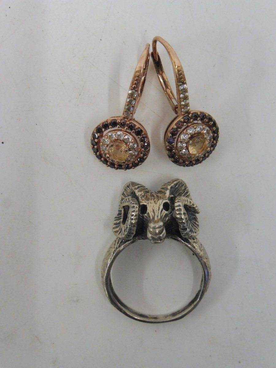 Lot 37 - A pair of unusual silver earrings and a white metal ring in the form of a ram's head.