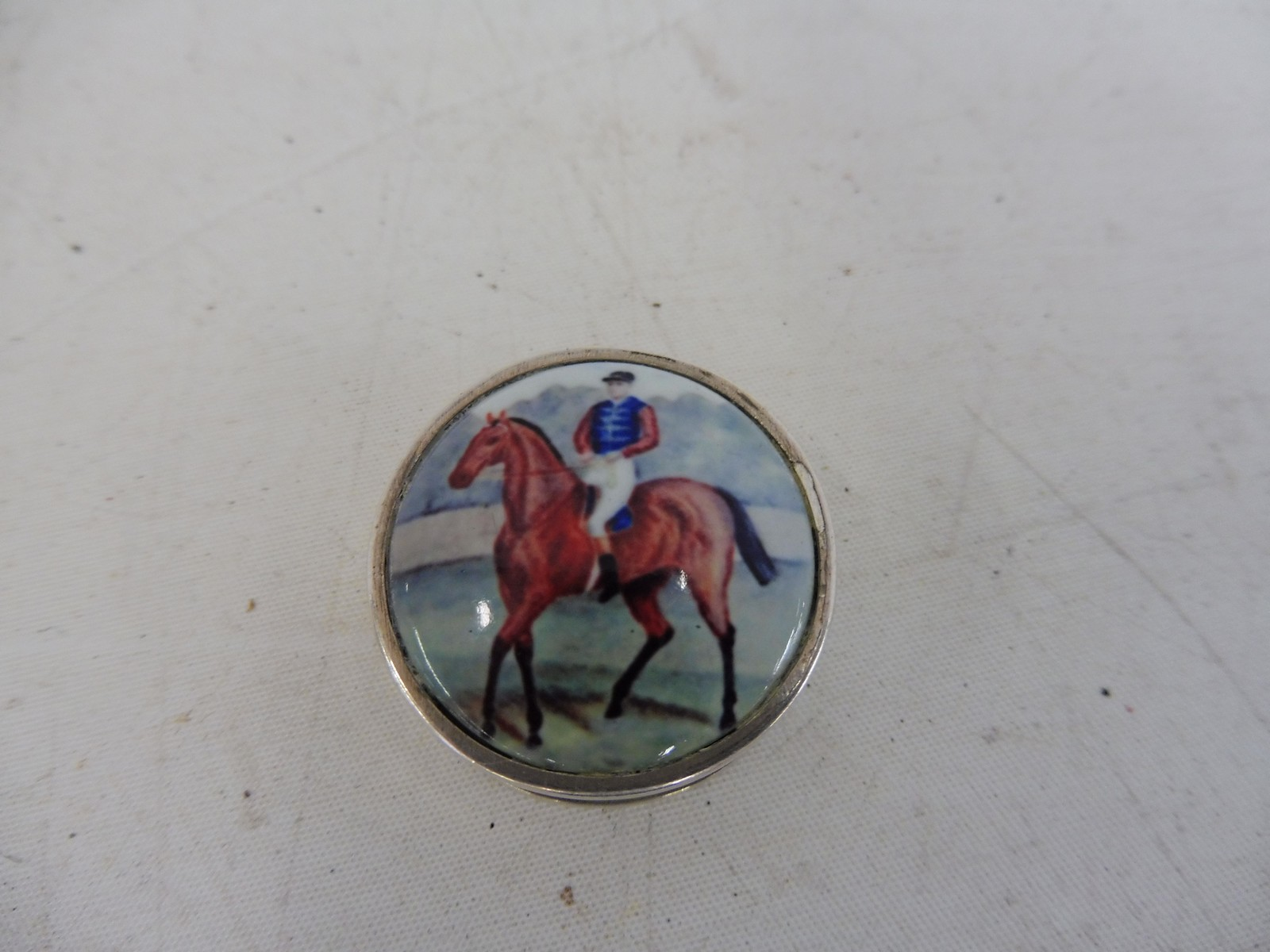 Lot 58 - A circular silver and enamel topped pill pot, the lid decorated with a jockey cantering on his