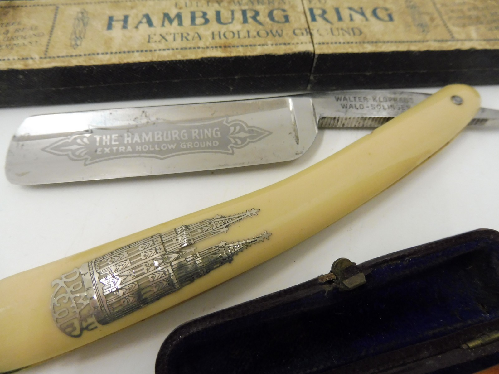 Lot 17 - A cased silver mounted cheroot holder and a cut throat razor engraved 'The Hamburg Ring'.