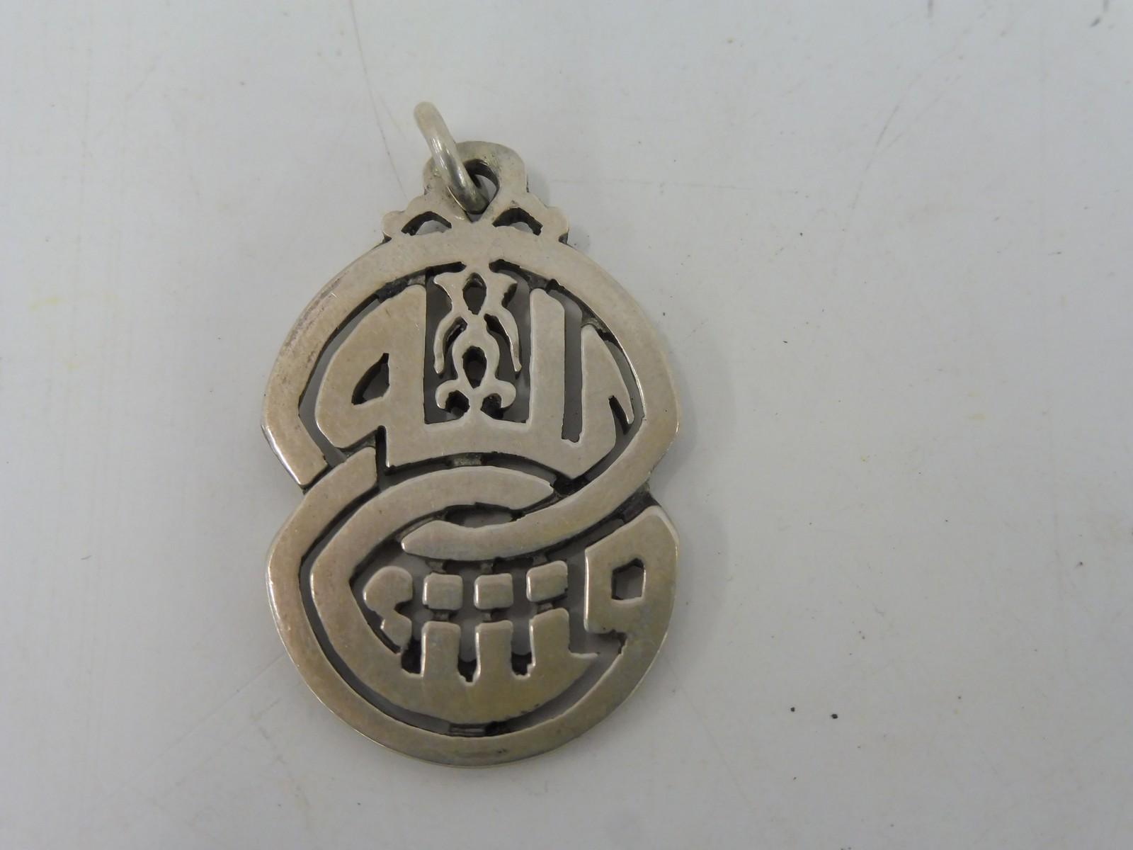 Lot 51 - An unusual Oriental white metal medallion.