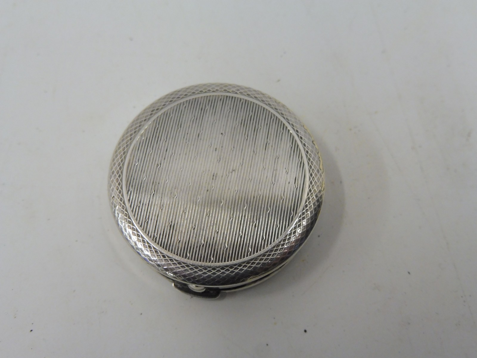 Lot 40 - A small circular silver pill pot with good quality engine turned decoration.