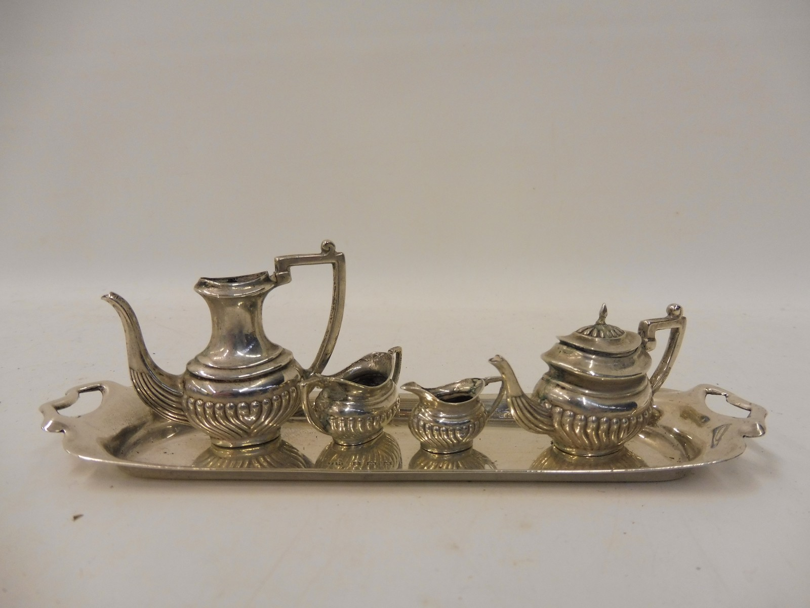 Lot 29 - A miniature silver four piece half fluted tea set on a rectangular tray.