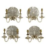 Lot 150 - Manner of the Cotswold School, a set of four Arts & Crafts style metal wall lights,