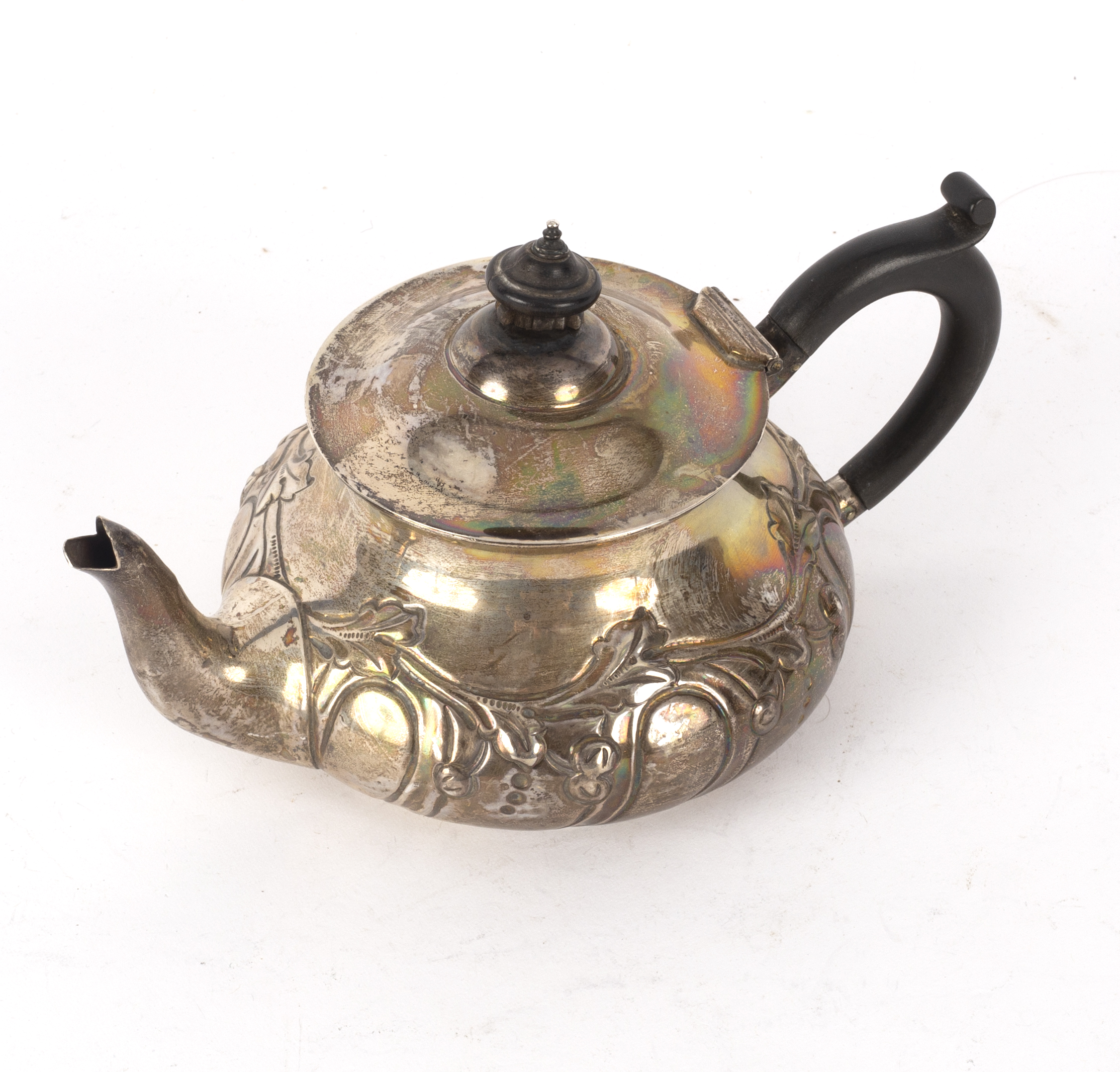 Lot 152 - A silver teapot, E & D, London 1905, of circular form embossed foliage,
