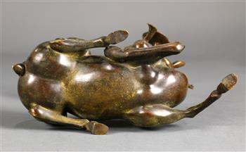 Lot 5022 - Chinese bronze sculpture of a deer, the recumbent animal clasping a large lingzhi sprig in its