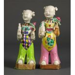 Lot 5001 - Pair of Chinese porcelain figures, each in the form of a child holding a sheng flute and a lotus