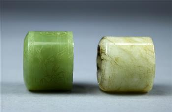 Lot 5039 - (lot of 2) Chinese hardstone thumb rings, one of celadon hue incised with bamboo; the other of off-