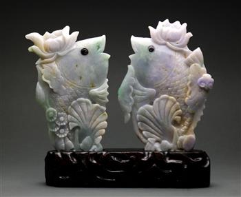 Lot 5029 - Pair of Chinese of jadeite fish, each topped with a lotus blossom on its head, and set into one wood