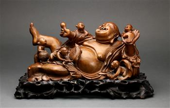 Lot 5046 - Chinese wooden sculpture, of reclining Budai holding a bat and jewel, surrounded by five playful