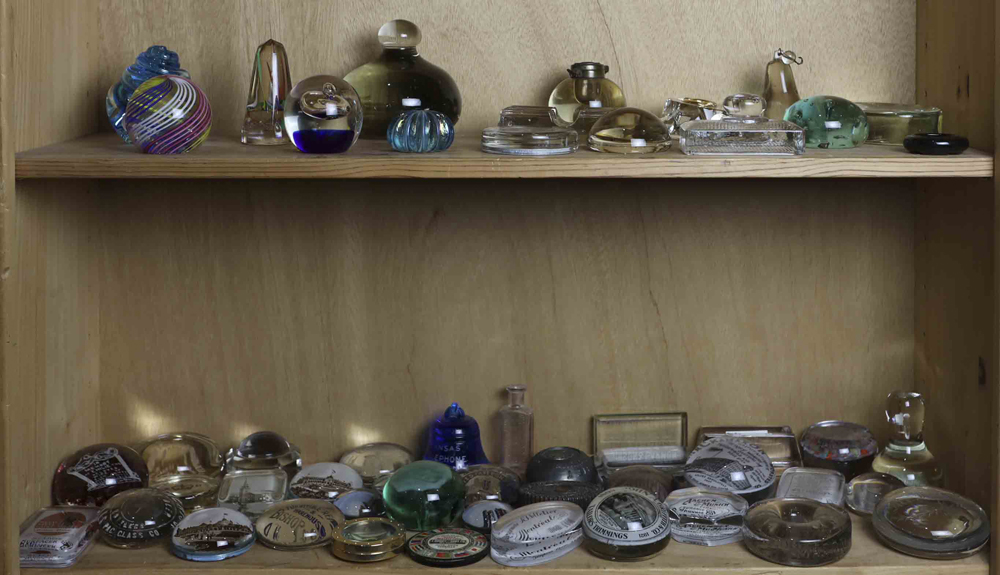 Lot 5758A - Two shelves of vintage retail and commemorative paperweights, including Shackamaxon Worsted Co.;