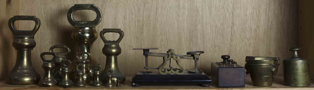 Lot 5747 - One shelf with a postage scale and assembled set of brass weights