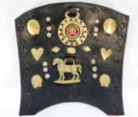 Lot 103 - An antique leather shield with various horse brass